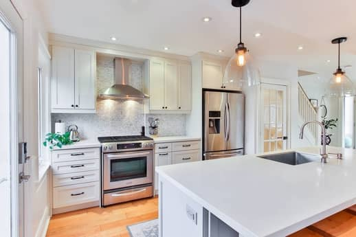 A picture of a light install in a white kitchen.